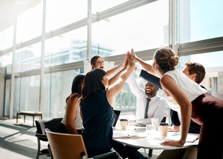 A team of real estate professionals giving a group high-five to stay motivated