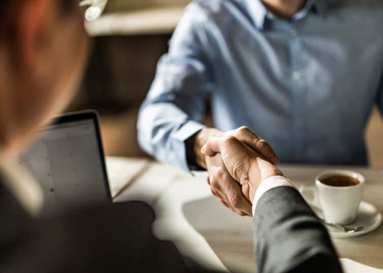 Newly licensed real estate broker shaking hands with a managing broker