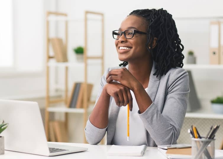 North Carolina mortgage loan officer smiling, sitting at desk in modern office