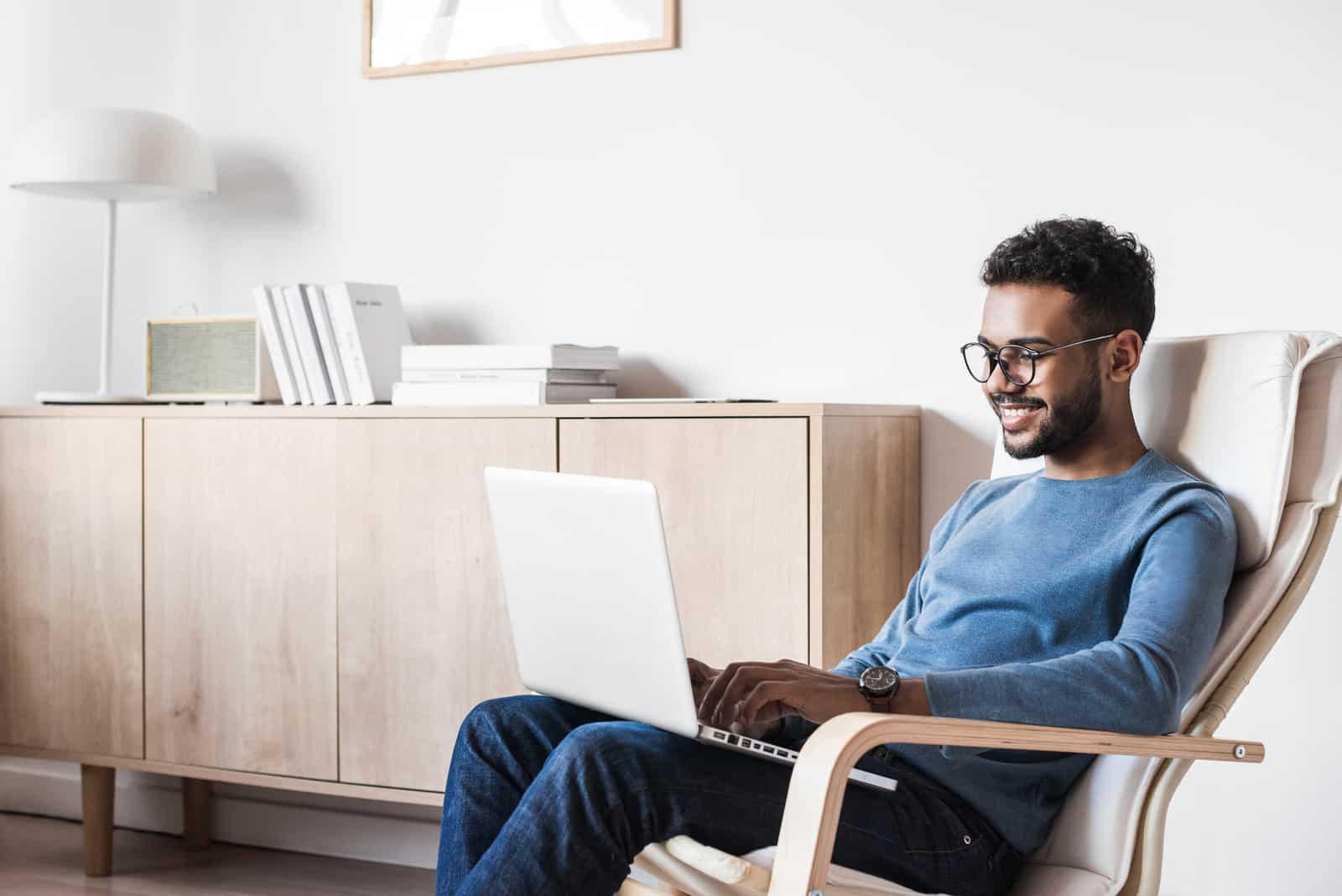 Cheerful man using laptop computer at home