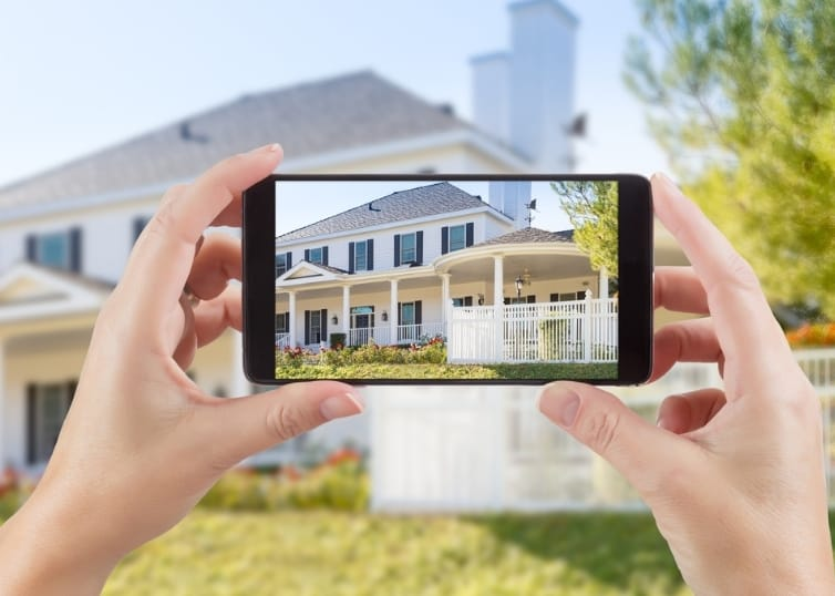 Woman's hands holding mobile phone to capture exterior real estate photos