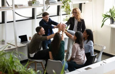 Diverse real estate staff giving high five demonstrating supportive brokerage culture
