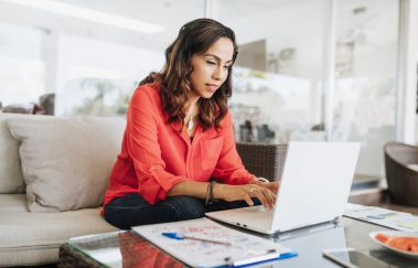 Latin American woman working on laptop, building a real estate broker website