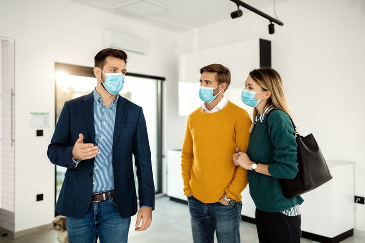Young couple and male real estate broker wearing face masks while looking a new home