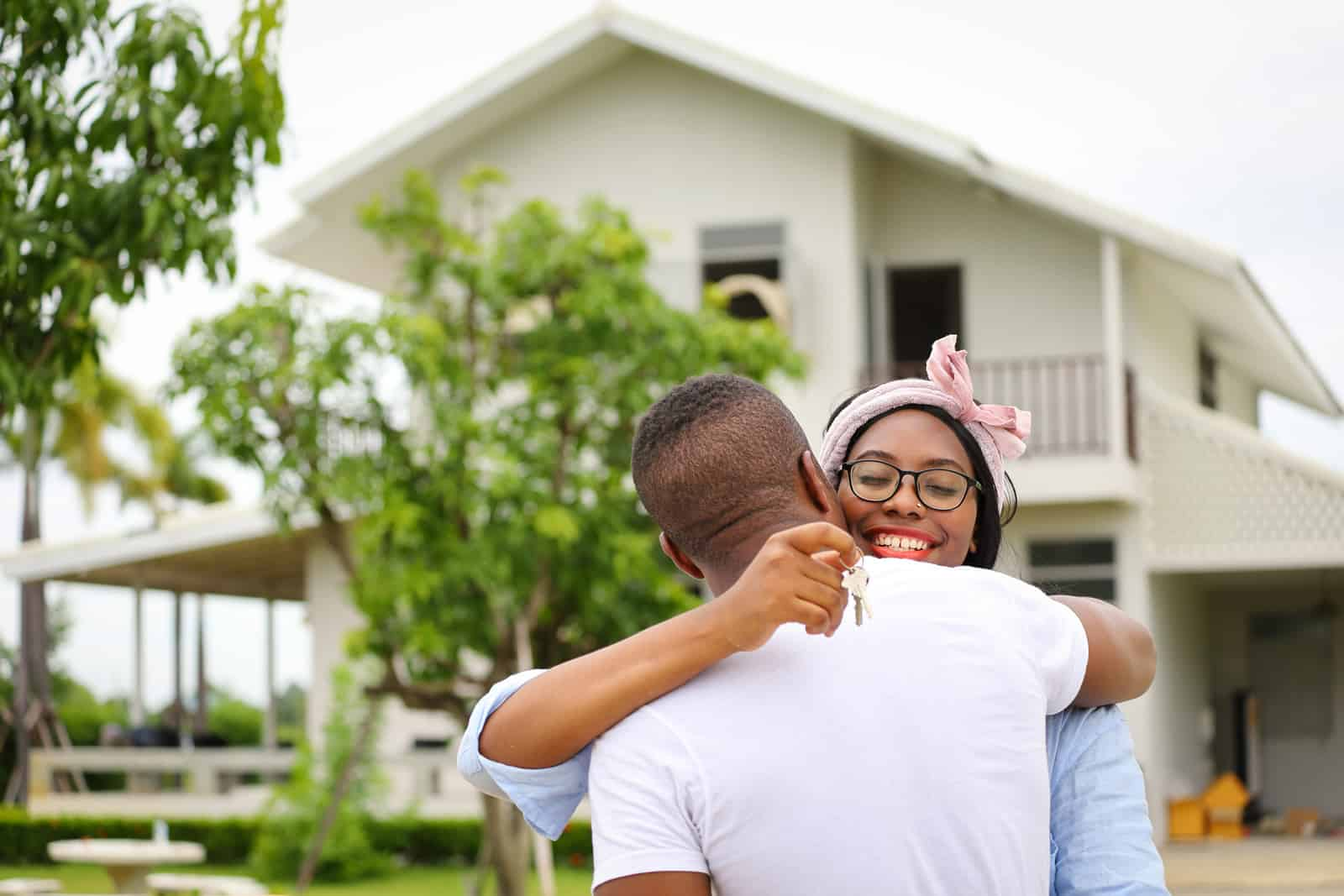 African American Generation Z homebuyers, young married couple hugging in front of the house they just bought