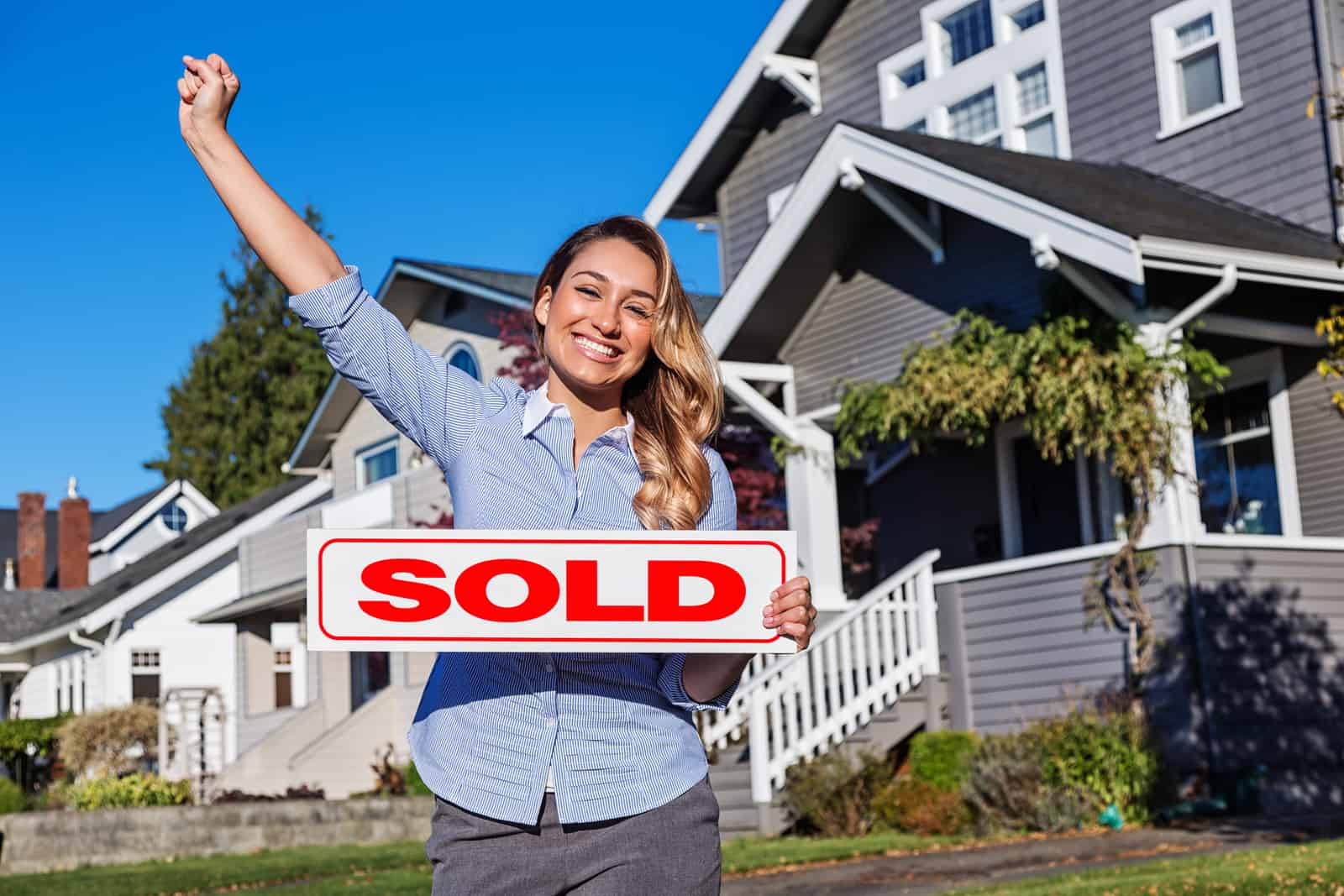 Young Hispanic Realtor with SOLD Sign