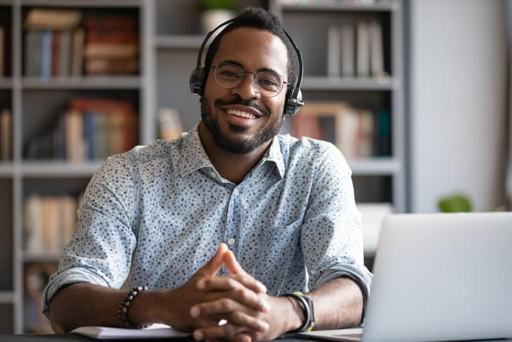African man wearing headphones sits at desk smiling, completing professional development course online